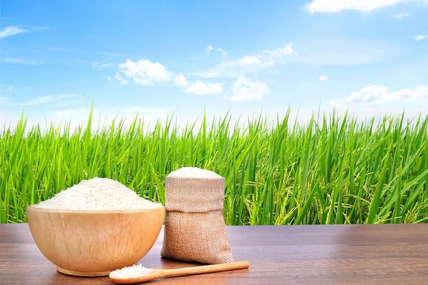 Jasmine rice na serapilheira de madeira da bacia e do pano de saco na tabela de madeira vintage com o campo verde do arroz.
