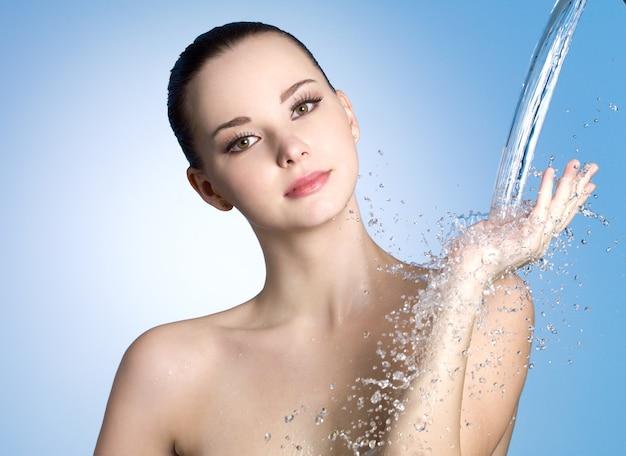 Jato de água para mulher jovem com pele limpa e fresca