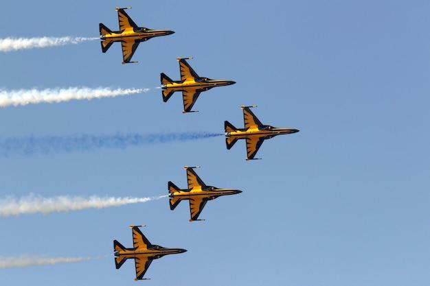 Jatos amarelos manobrando no céu durante um desfile aéreo