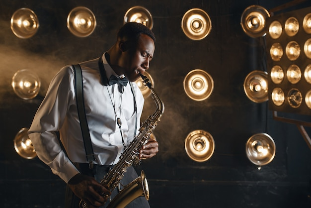Jazzman masculino toca saxofone no palco com holofotes. músico de jazz negro se apresentando na cena