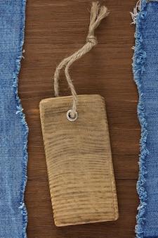 Jean azul e etiqueta de preço em fundo de textura de madeira