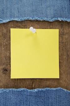 Jean azul e papel de nota em textura de madeira