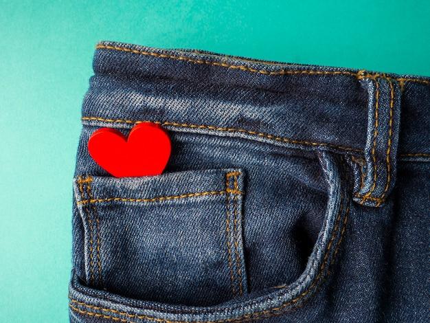 Jeans azuis e um coração vermelho estão no bolso da frente de jeans em verde