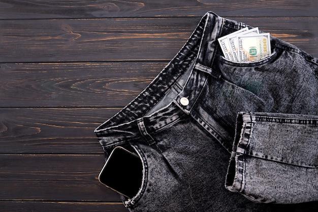 Jeans cinza com dólares e um smartphone nos bolsos em um fundo escuro de madeira com espaço de cópia. plnerovka plana