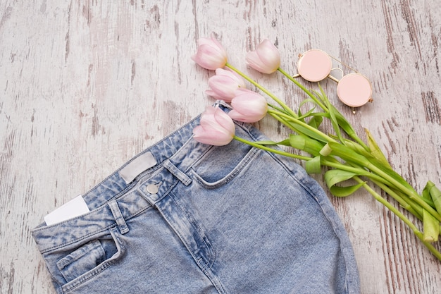 Jeans com etiqueta limpa e tulipas em uma superfície de madeira