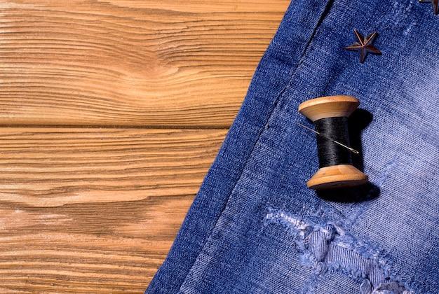 Jeans com fios em um espaço de madeira. copie o espaço. costura conceito de restauração de coisas antigas