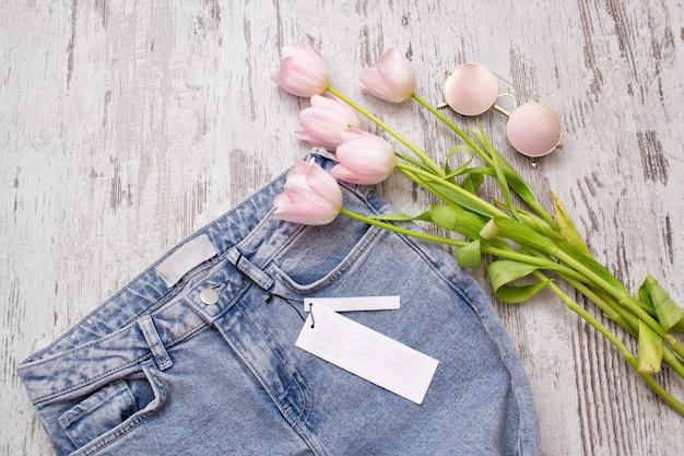 Jeans com uma etiqueta limpa, óculos cor de rosa e tulipas