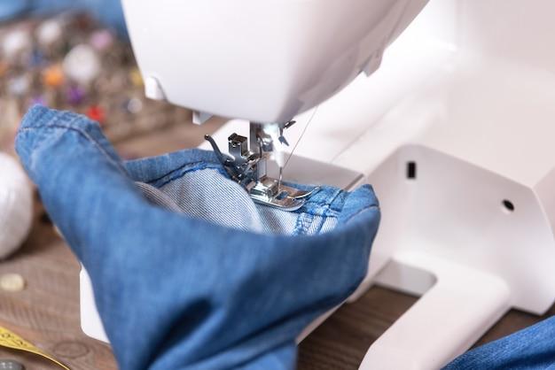 Jeans de costura com máquina de costura. reparação de jeans por máquina de costura.