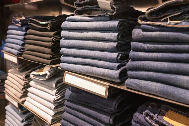 Jeans de diferentes cores, texturas e tons ficam em pilhas arrumadas no balcão da vitrine da loja de moda da marca