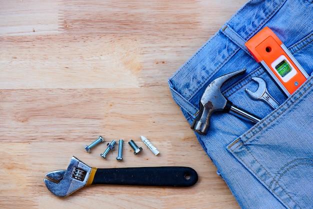 Jeans e ferramenta de equipamento de construção no chão de madeira