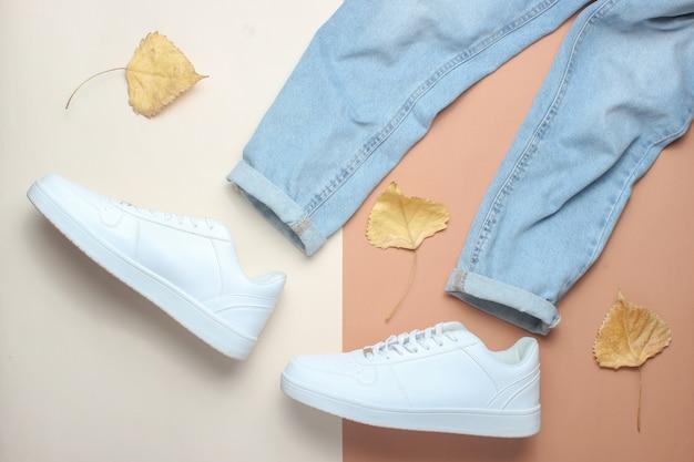 Jeans e tênis branco entre as folhas caídas. minimalismo, vista superior.