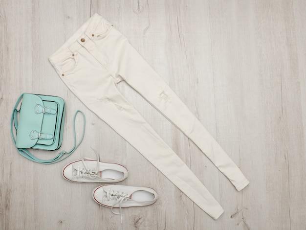 Jeans e tênis brancos, bolsa de menta ... superfície de madeira.