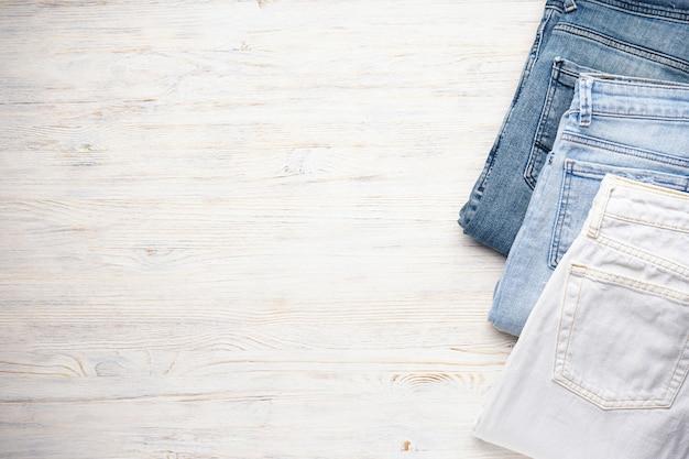 Jeans empilhados sobre uma mesa de madeira, plana. coloque o texto distante.