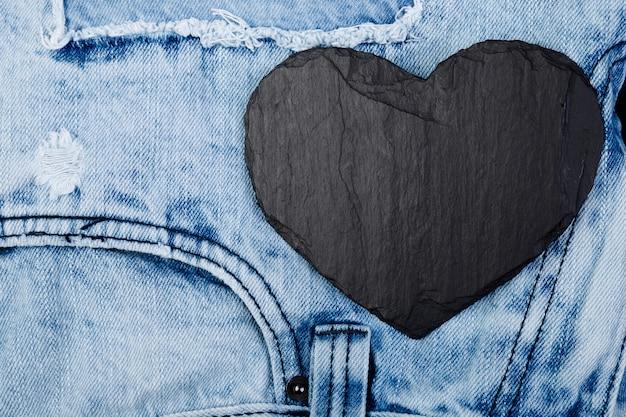 Jeans. fundo de textura de calça jeans. dia dos namorados. coração de ardósia de pedra preta. copyspace.