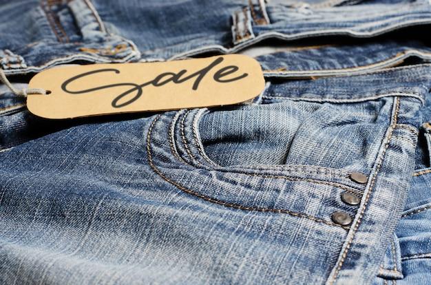 Jeans. jeans azul no balcão da loja. venda - inscrição manuscrita em uma etiqueta de papel.