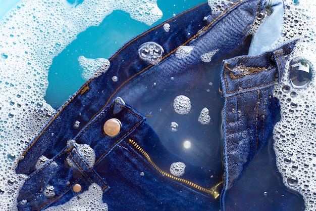 Jeans mergulhar em dissolução de detergente em pó. conceito de roupa