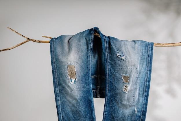 Jeans, moda, conserto ou conceito de pano diy. calça jeans calça pendurada no galho de árvore seca. sombreamento na parede branca. estilo de trabalho patch