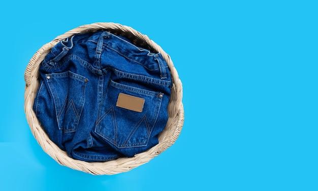 Jeans no cesto de roupa suja em fundo azul. vista do topo