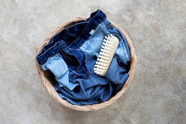 Jeans no cesto de roupa suja no fundo do chão de cimento.