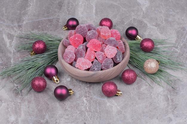 Jellybeans multicoloridos em um copo de madeira no mármore