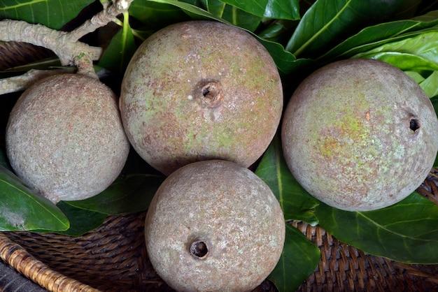 Jenipapo de frutas com folhas na cesta de vime