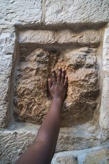Jerusalém, israel. tocando a pedra sagrada na via dolorosa. impressão da mão de jesus.