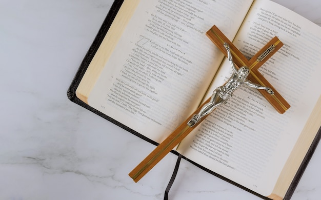 Jesus a caminho de deus por meio da oração com a cruz é colocado no topo da bíblia sagrada.