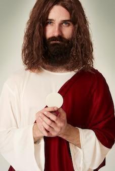 Jesus com o objeto sagrado que é hóstia