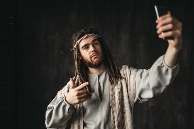 Jesus cristo faz selfie no telefone no escuro