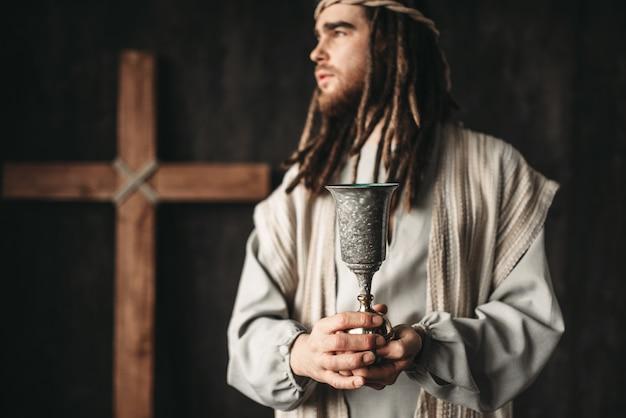 Jesus cristo segura uma taça de vinho, símbolo da fé cristã, cruz da crucificação no preto