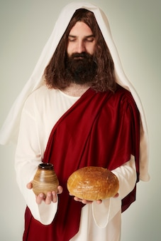 Jesus de olhos fechados segurando vinho e pão