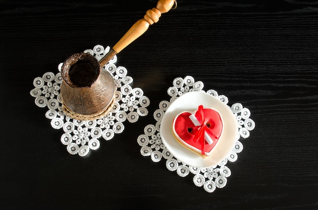 Jezva com café, pires com pão de mel vermelho em forma de coração sobre superfície de madeira preta. vista do topo