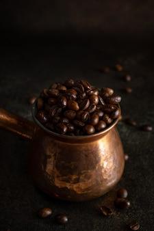 Jezve de cobre com grãos de café kopi luwak na superfície marrom escura, vista closeup
