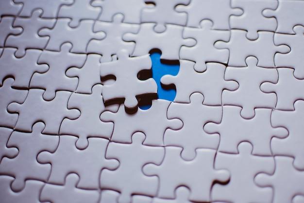 Jigsaw com um pedaço faltando revelando fundo azul
