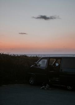 Jipe em uma praia sob um céu laranja