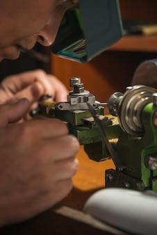 Joalheiro com lentes de aumento corta uma peça na máquina