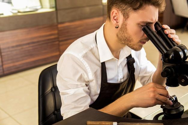 Joalheiro examina o anel através de um microscópio
