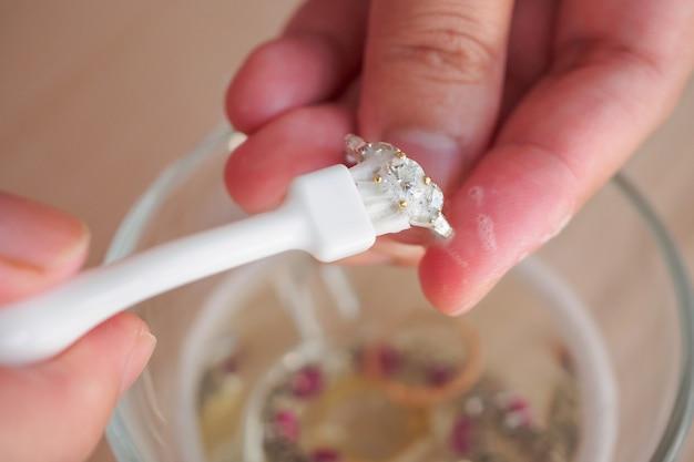 Joalheiro limpando e polindo as mãos de joias vintage com anel de diamante close up