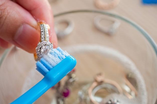 Joalheiro limpando e polindo as mãos de joias vintage com anel de diamante closeup