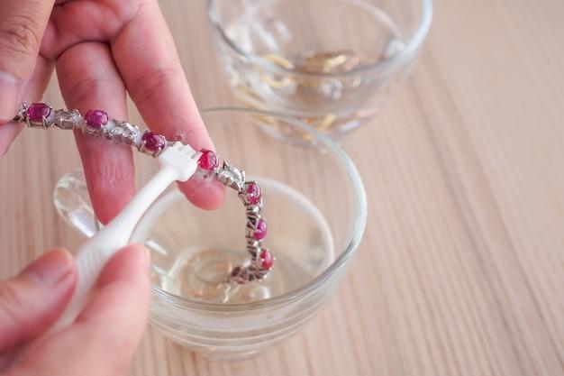 Joalheiro limpando e polindo as mãos de joias vintage com pulseira de rubi vermelho close up