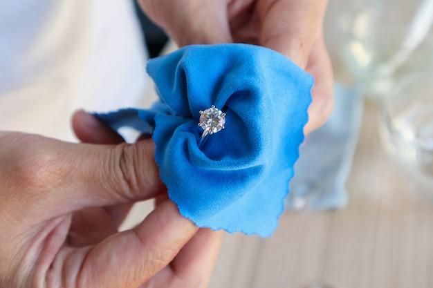 Joalheiro, polindo e limpando manualmente joias de diamante com tecido de microfibra