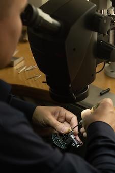 Joalheiro profissional no trabalho. o joalheiro olha no microscópio e decora o anel precioso com lindas pedras preciosas.