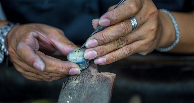 Joalheiro tailandês, lida com joias e pedras preciosas na oficina, processo de fabricação de joias, close-up