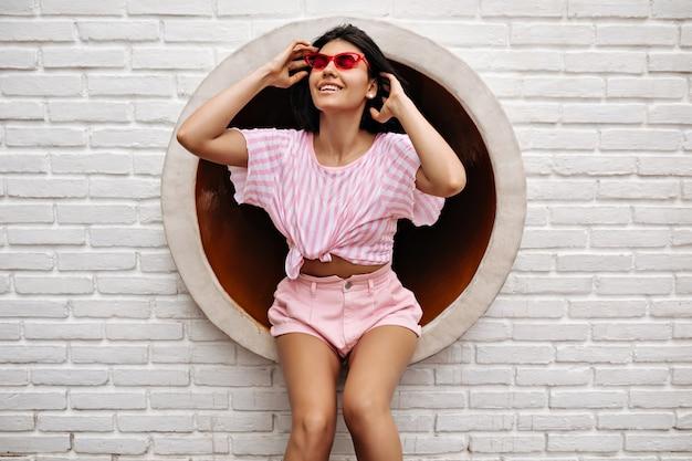Jocund bronzeada mulher rindo no meio urbano. mulher animada sentada na parede de tijolos brancos.
