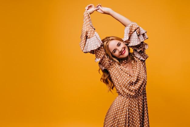 Jocund modelo feminino em elegante traje vintage sorrindo. foto interna de mulher loira satisfeita isolada na parede amarela.
