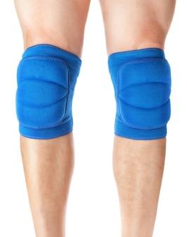 Joelheiras para proteger os jogos nas pernas masculinas. em uma parede branca.