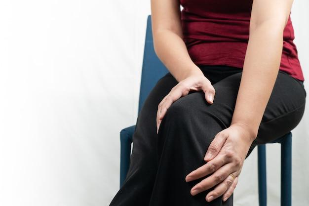 Joelho das mulheres dolorido, mulheres tocam o joelho com dor em casa