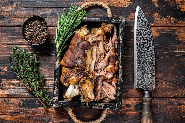 Joelho de porco assado eisbein em uma bandeja de madeira com faca. fundo de madeira escuro. vista do topo.