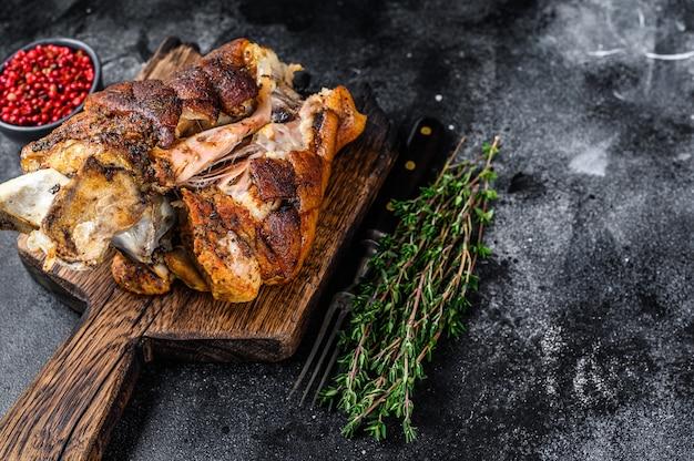 Joelho de porco assado eisbein em uma placa de madeira com ervas