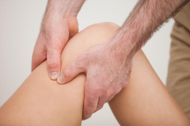 Joelho de um paciente sendo segurado por um fisioterapeuta